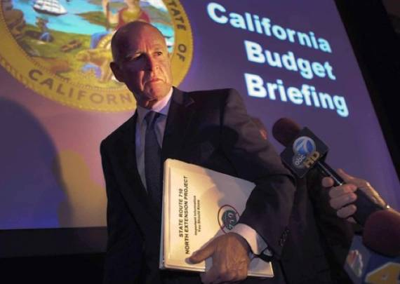 """That's not a doctored photo.  Brown leaves a budget briefing carrying a """"No on 710"""" binder.  Photo: (Brian van der Brug / Los Angeles Times / December 14, 2010) via ##http://la.curbed.com/archives/2010/12/doing_his_homework.php##Curbed##"""