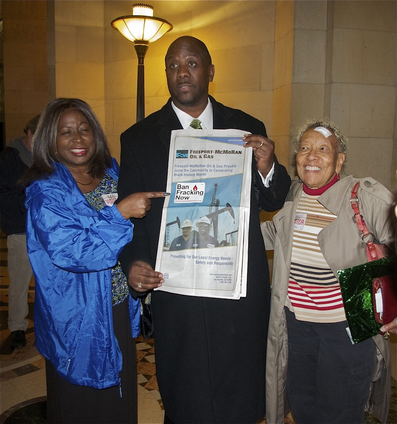 Pastor Kevin Sauls and members of Holman Church place a Ban Fracking Now sticker on the full page ad Freeport McMoRan Oil & Gas took out in the LA Sentinel in anticipation of the City Council vote. Sahra Sulaiman/LA Streetsblog