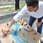 Councilmember Felipe Fuentes of the seventh district of Los Angeles adjusts the far end of a 12-foot model of the Pacoima Wash. Fuentes created adjusted the model to favor recreation, equestrian uses, and have greater accessibility to the Pacoima Wash.