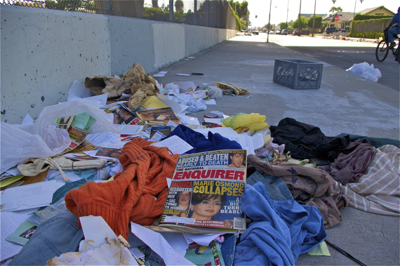 Piles of random clothing and issues of the National Enquirer from the year 2000 (at the overpass at 52nd and Broadway) Sahra Sulaiman/Streetsblog LA