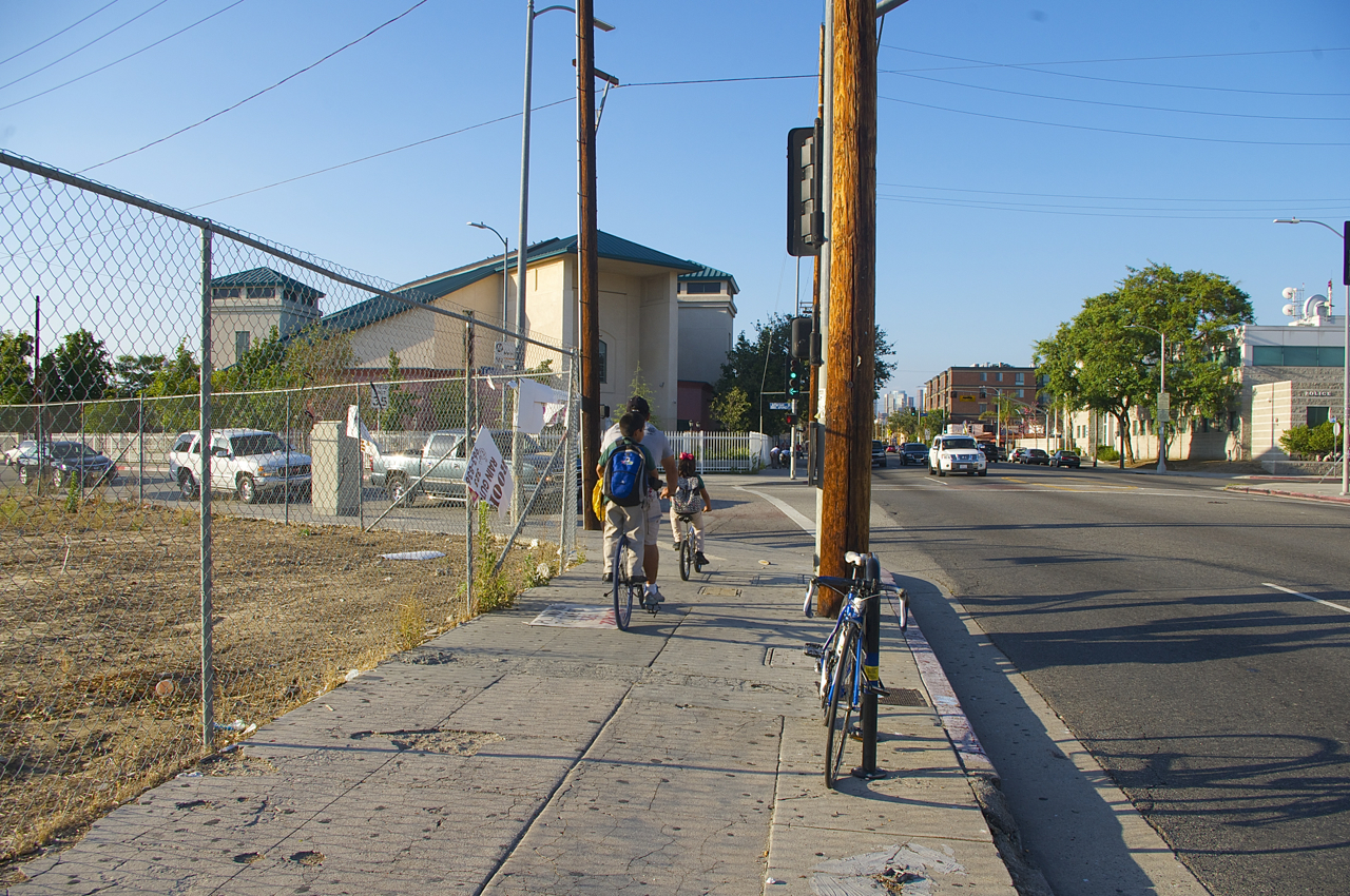A father runs errands with his children along Central Avenue after picking them up from school. Sahra Sulaiman/Streetsblog L.A.