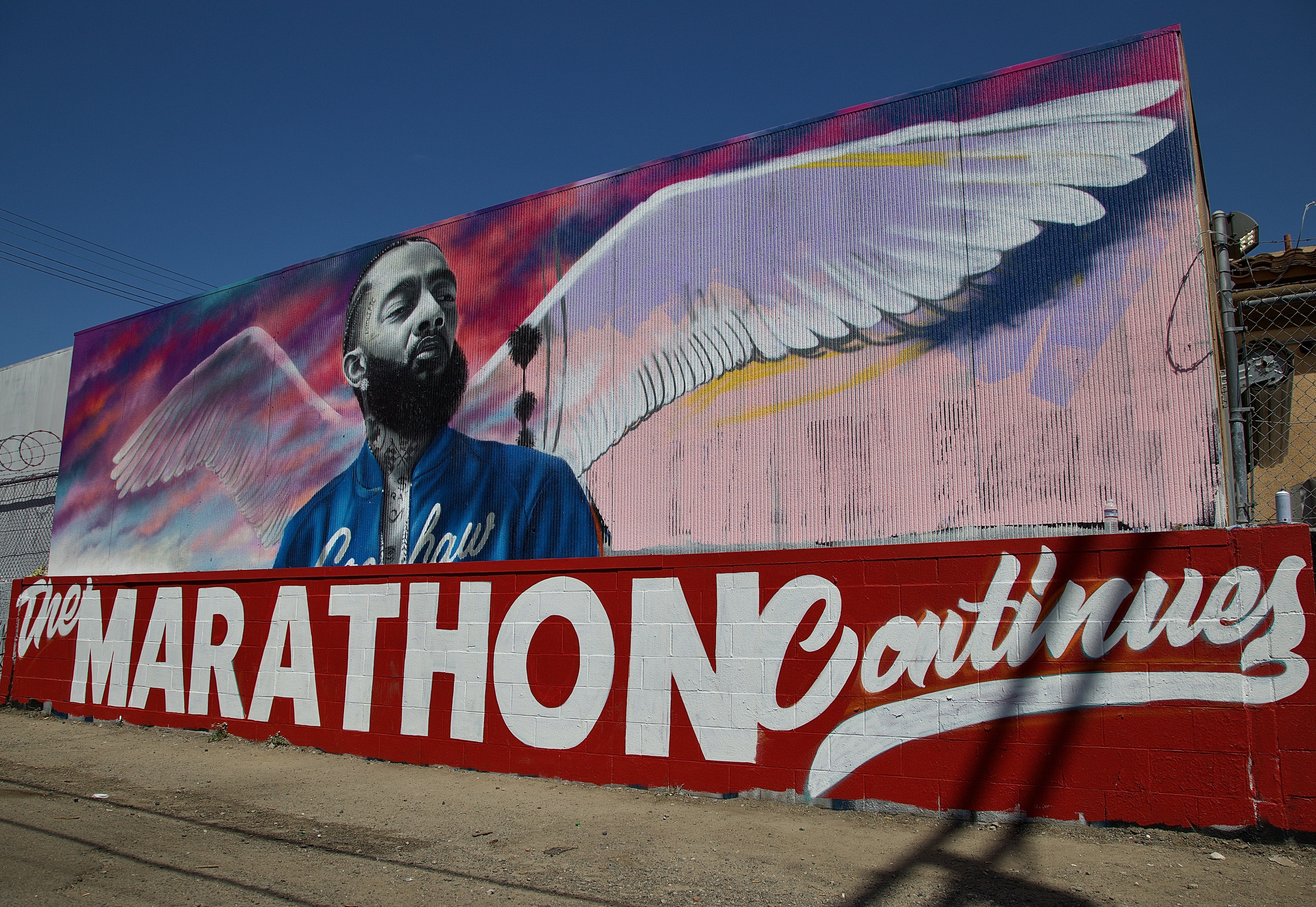 """A portrait of Nipsey Hussle by artist Danny Mateo graces the alley adjacent to the strip mall where Hussle was killed at Crenshaw and Slauson on March 31. """"The Marathon Continues"""" references both his approach to building his career from the ground up and his understanding of what it took to bring the community along with him. Sahra Sulaiman/Streetsblog L.A."""