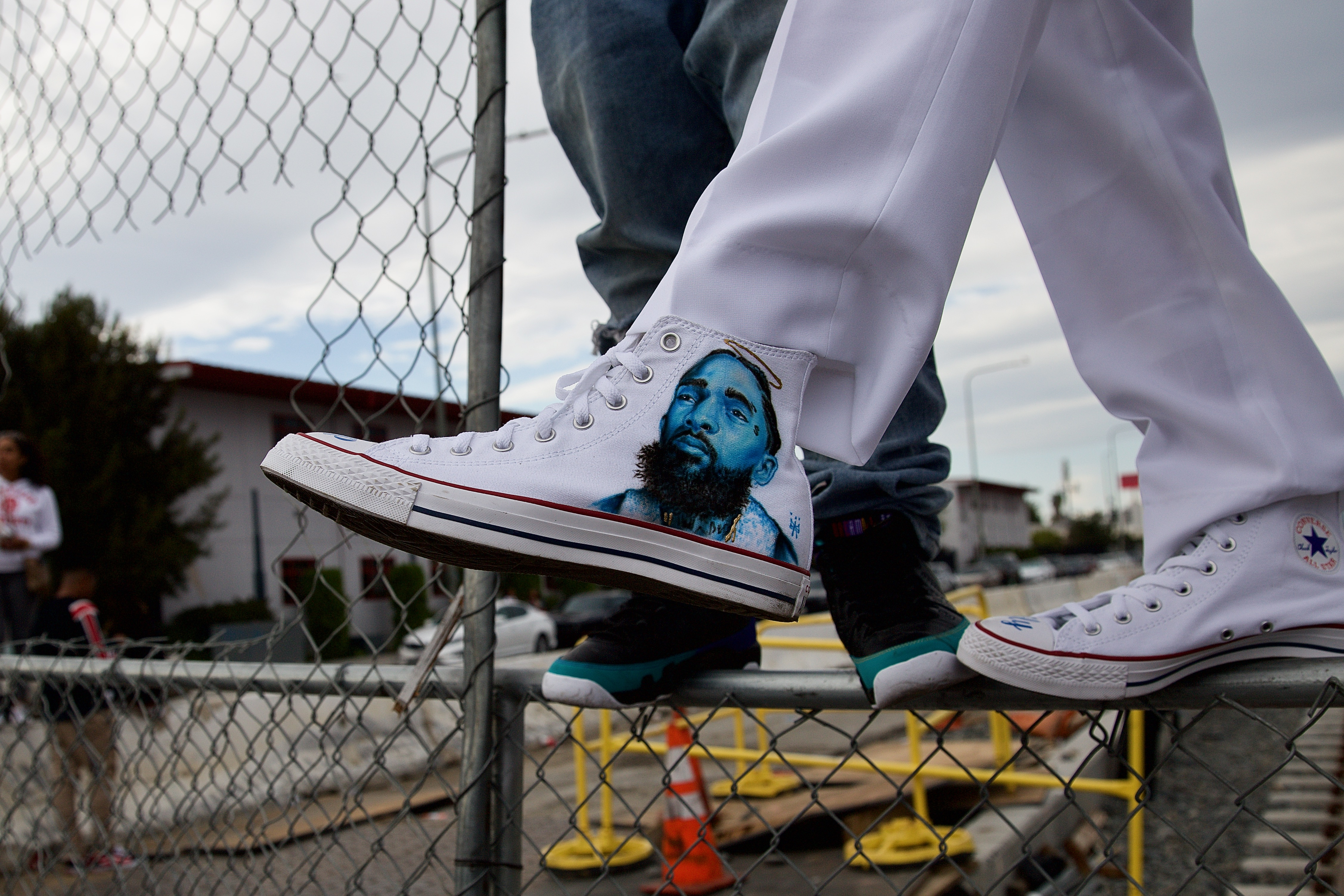 Jermaine Welch shows off the shoe he had custom painted in Nipsey Hussle's honor while waiting for Hussle's funeral procession to pass through the intersection at Crenshaw and Slauson on April 11. Hussle was killed in front of his store, The Marathon, on March 31. Sahra Sulaiman/Streetsblog L.A.