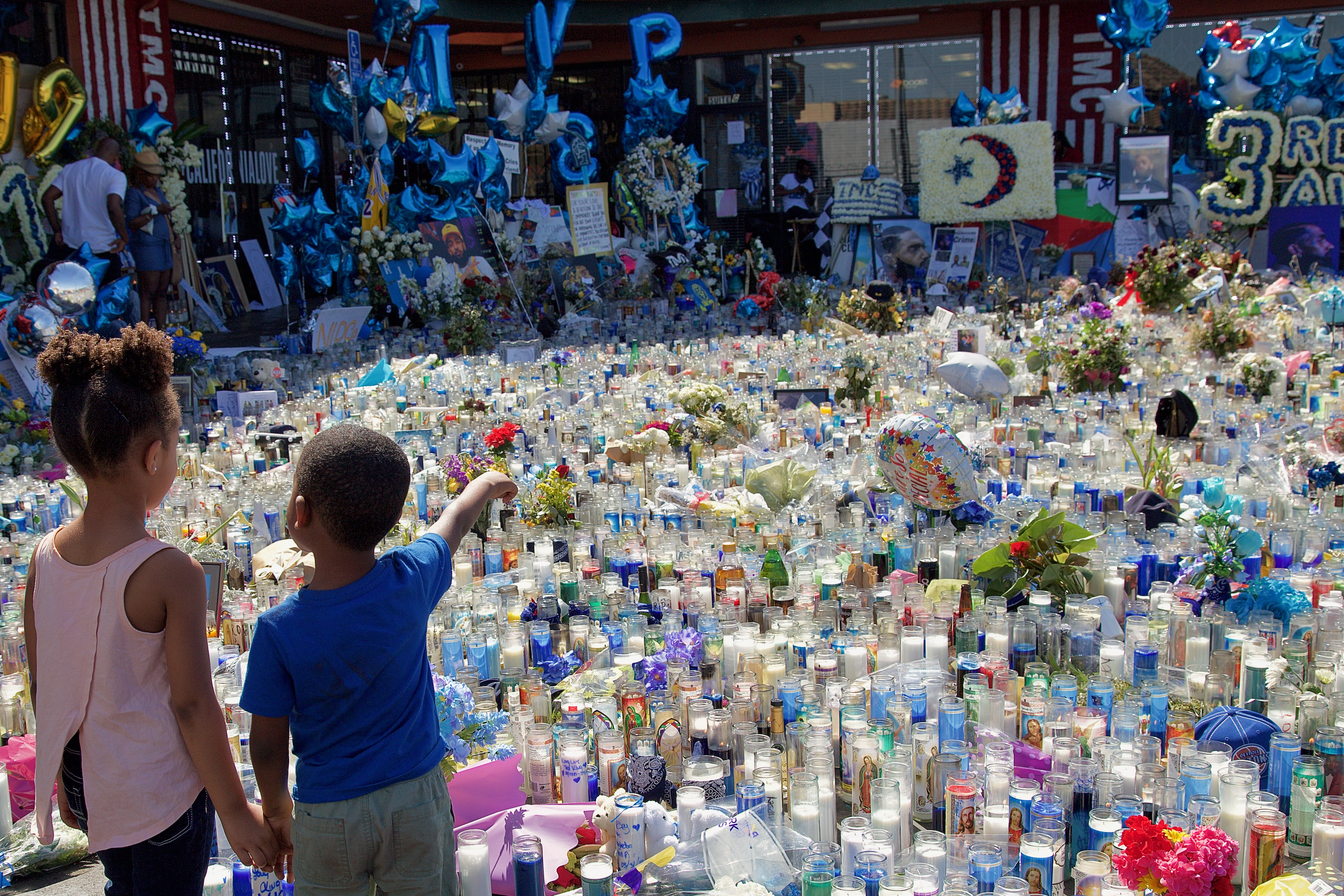 The memorial to Nipsey Hussle sits in front of The Marathon store in the strip mall where he spent much of his life and where he worked to uplift the community. He died here March 31. Sahra Sulaiman/Streetsblog L.A.